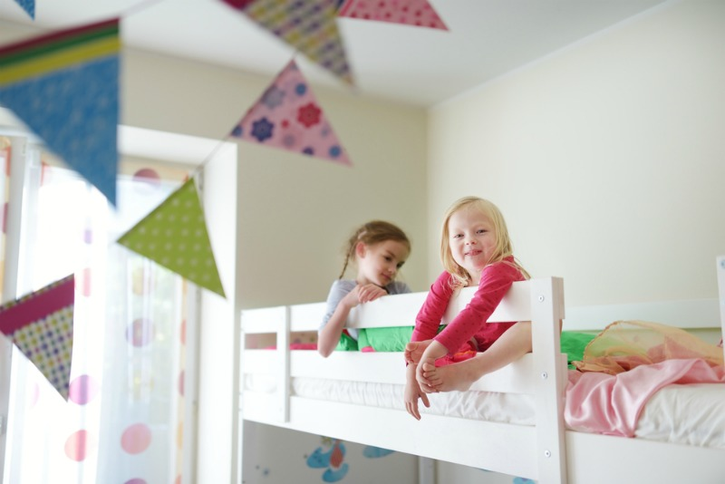 An image of two children sat on a bunk bed thats normal height