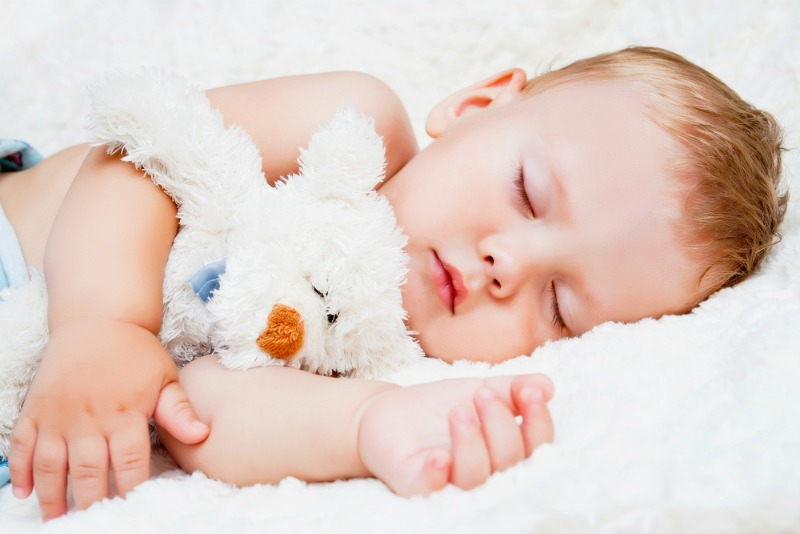 Image of baby sleeping with teddy in a baby's room at right room temperature for babies