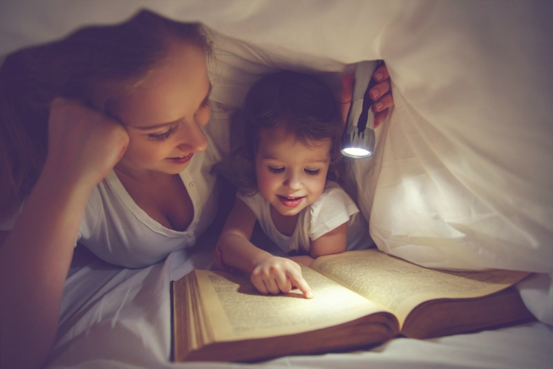 An image showing a parent reading to a child