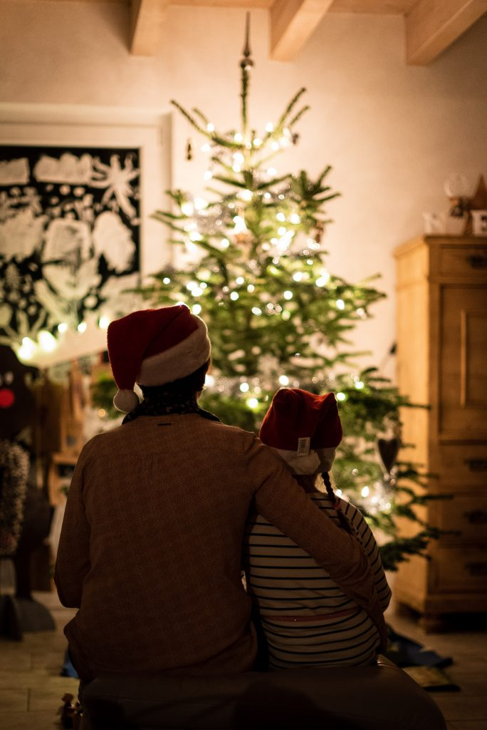 Parent AAnd Child With Christmas Hats With Christmas Tree