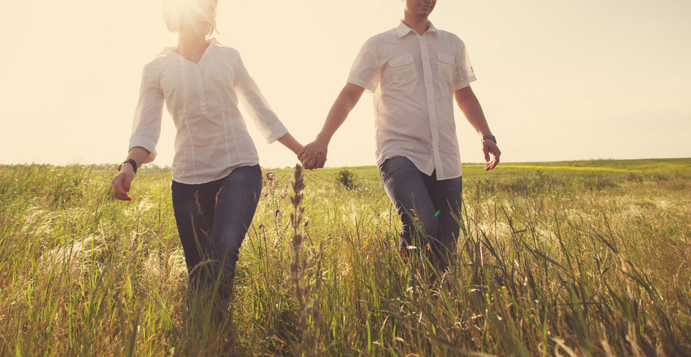 Couple Walking Through Field During Allergy Season. Read more on how to sleep better during allergy season at Sleep Matters Club