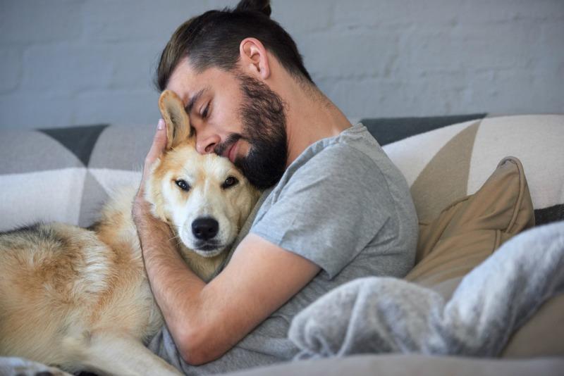Image of man cuddling dog