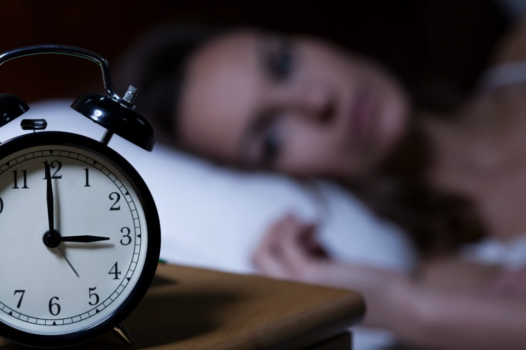 clock at early morning with woman unable to sleep