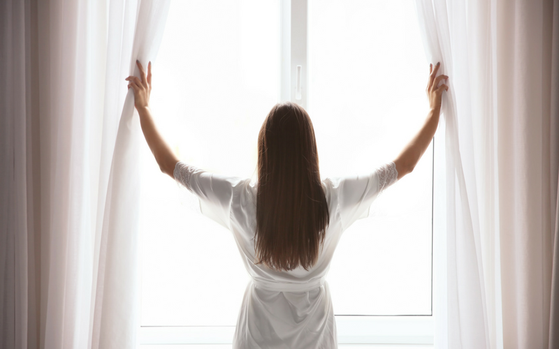 Image of woman opening curtains