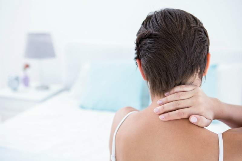 A woman suffering from neck pain in bed