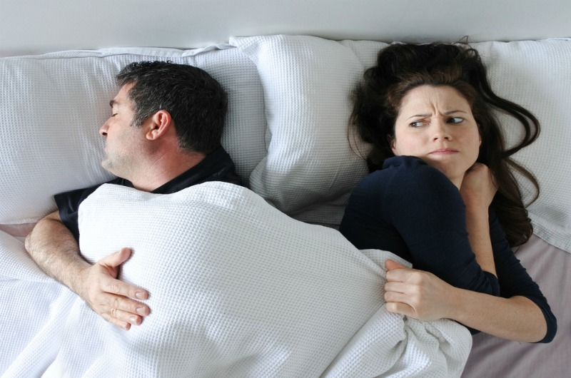 Image of couple in bed with partner sleep difficulties