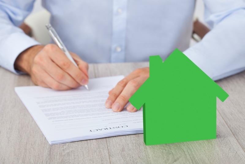 image of man signing property documents