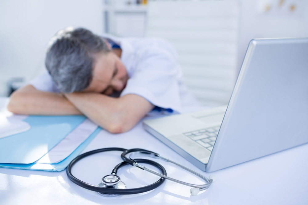 Doctor Sleeping on Desk - Is he sleep deprived? Find out at Sleep Matters Club