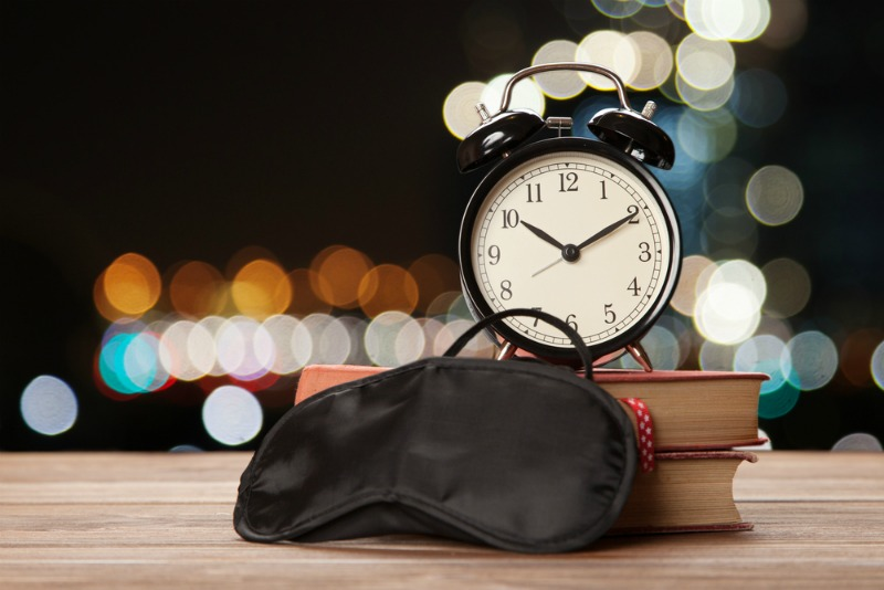 An image showing a sleeping mask, books and alarm clock