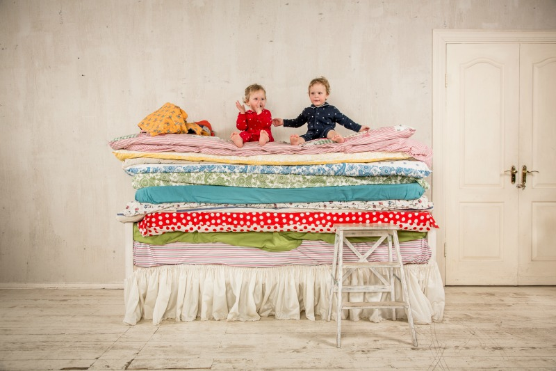 An image of two children sat on a tall bed showing bed height