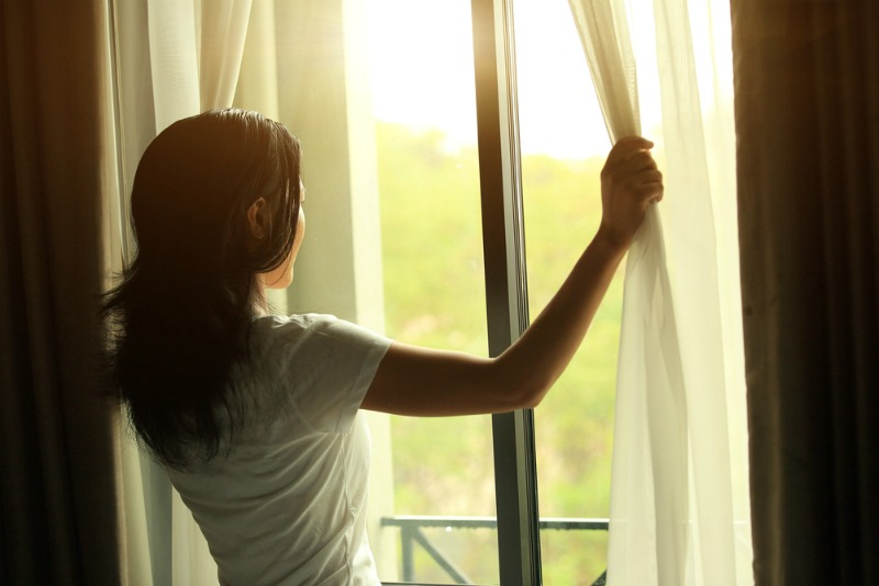 An image of a woman opening curtains