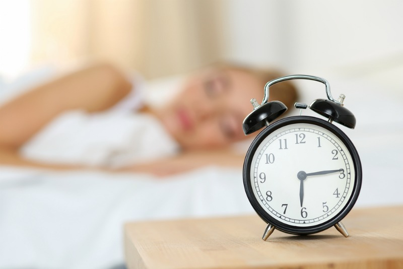 image shows a clock and woman sleeping to identify how clocks going back affects sleep