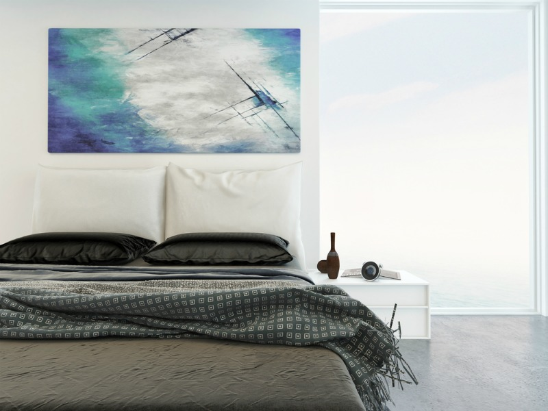 Bed with artwork hanging above it