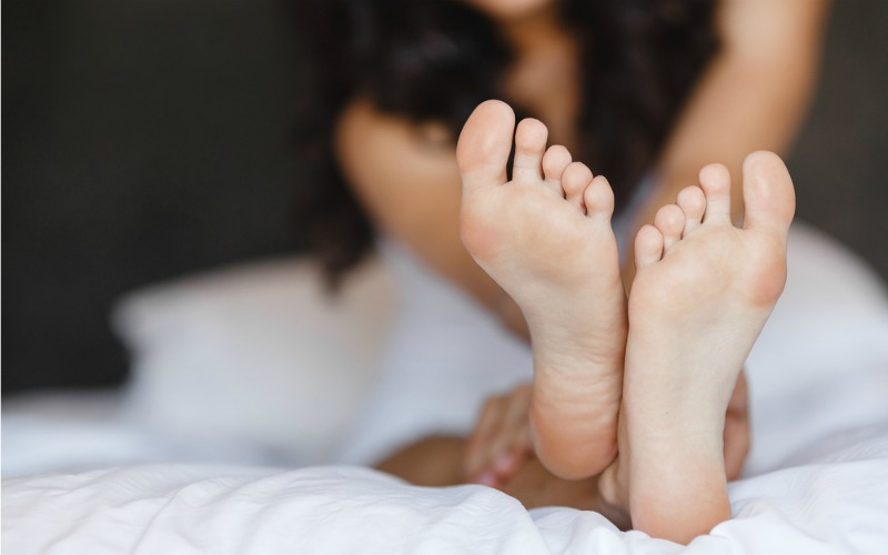 Close up of feet on bed