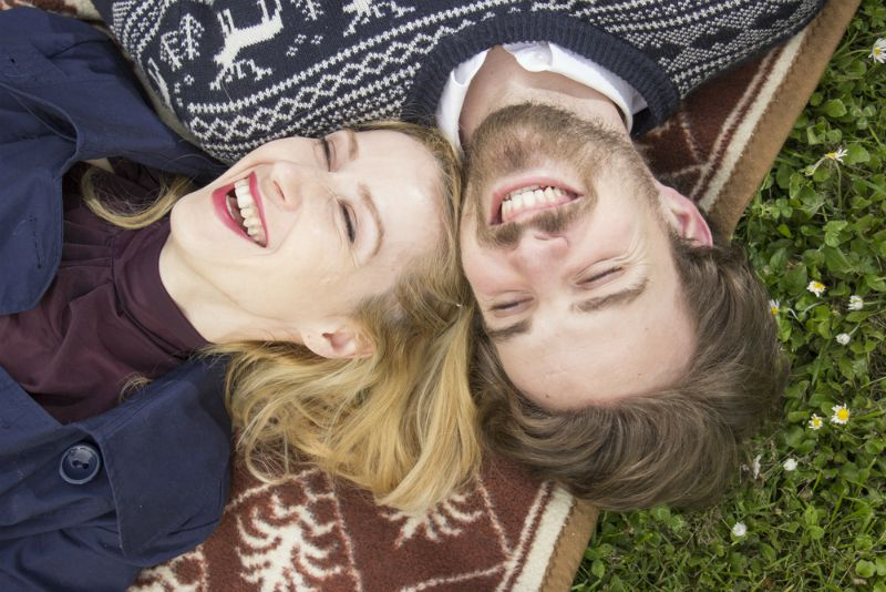 Happy couple lying on grass laughing