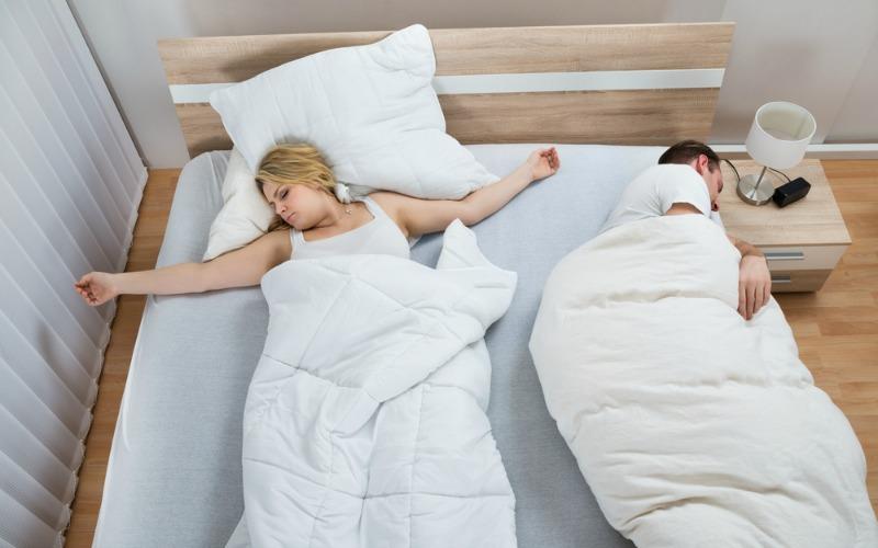 Couple struggling to sleep due to heat