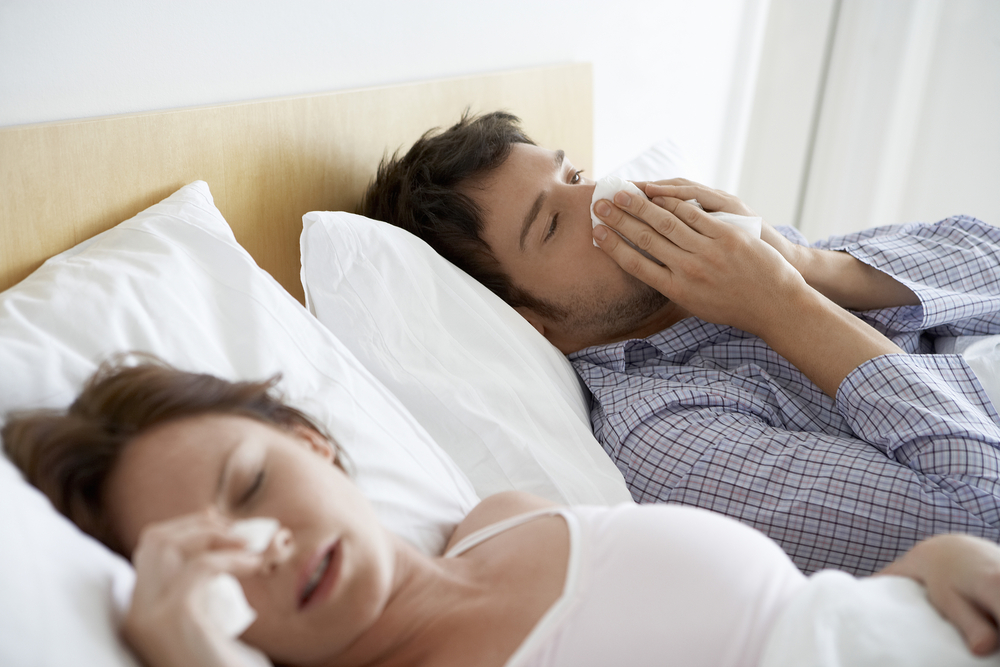 couple in bed with tissues as they are suffering from hayfever