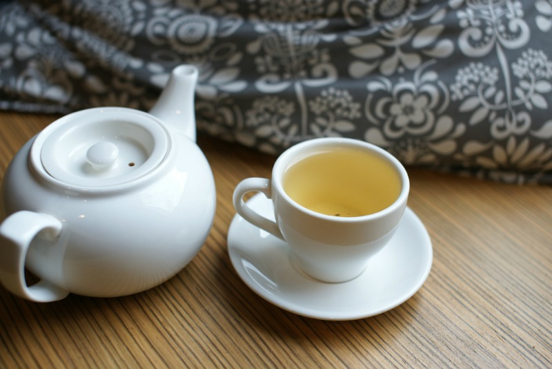 Cup of tea next to a bed