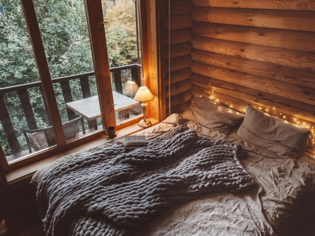 hygge bedroom to show hygge decor with chunky knitted throw, pillows and warm lighting