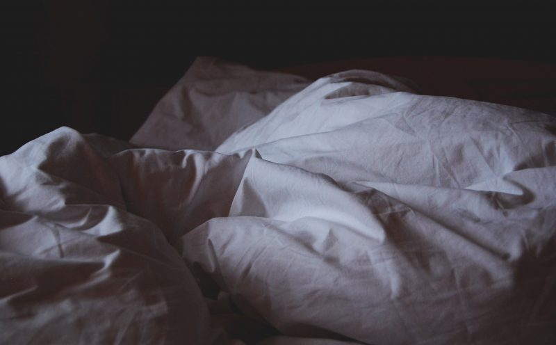 abstract image of disturbed pillows and duvet to show insomnia in elderly