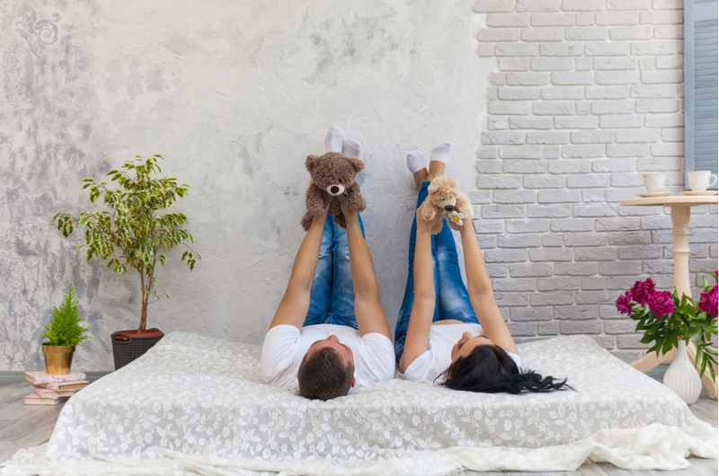 Man and woman with teddies on bed