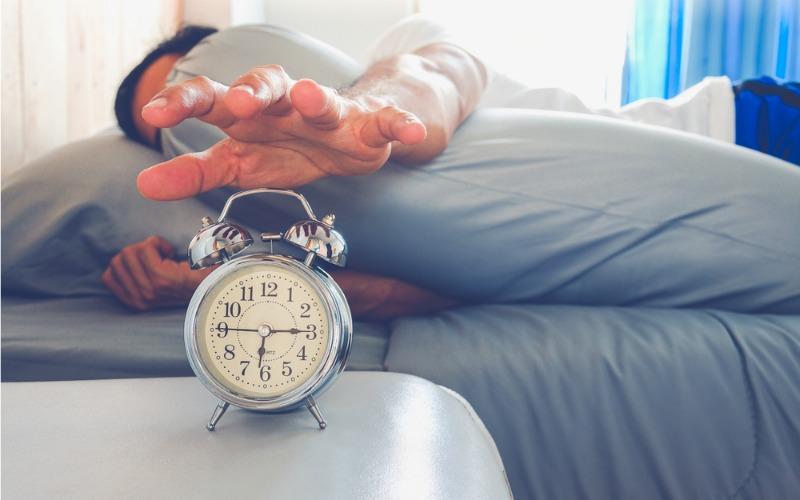 man oversleeping and snoozing alarm