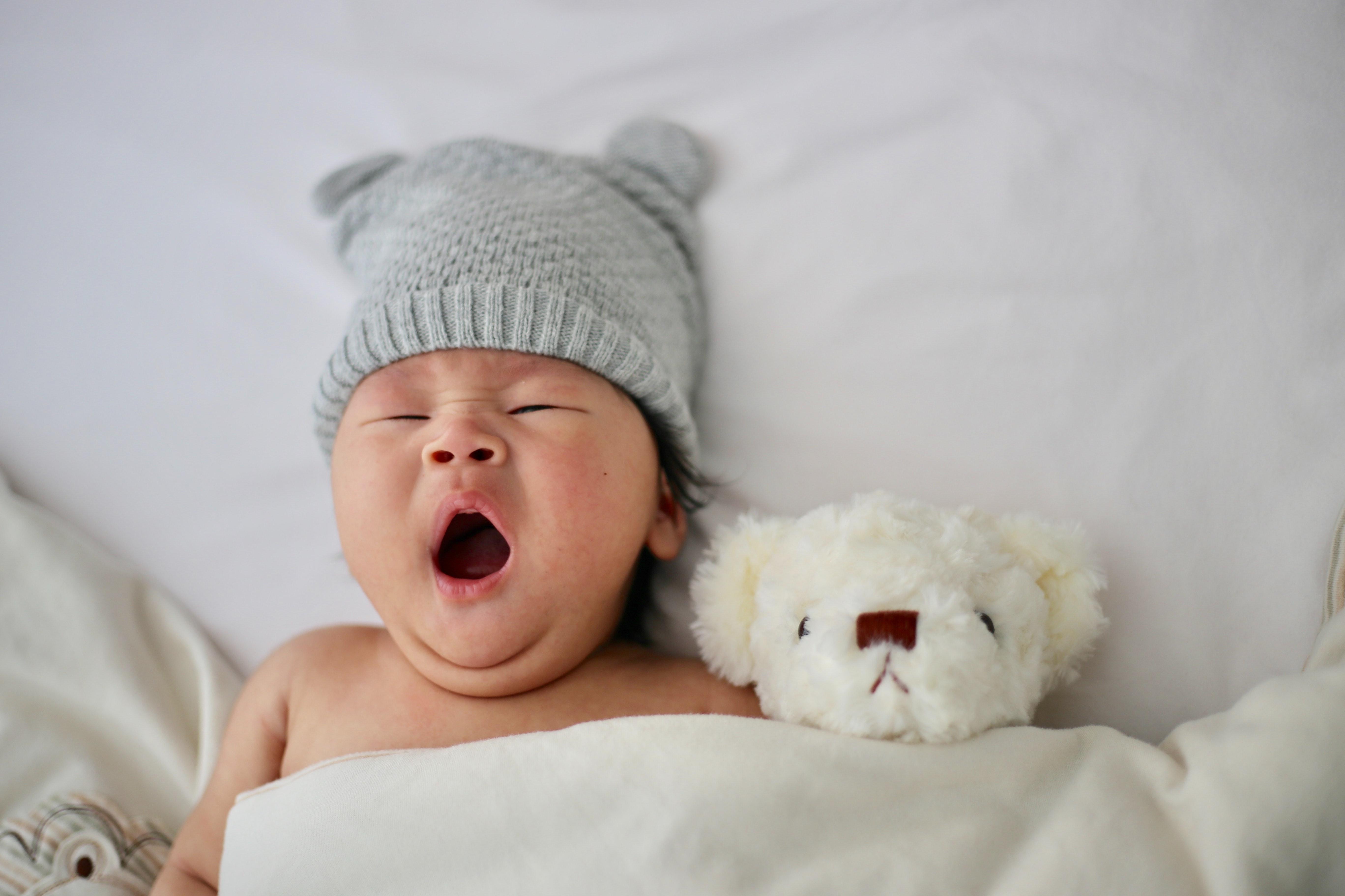 baby yawning next to teddy bear