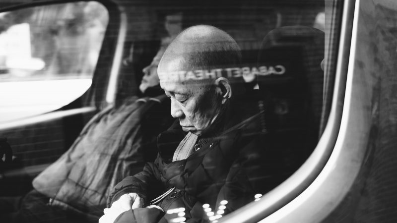 elderly man asleep on train after struggling with insomnia
