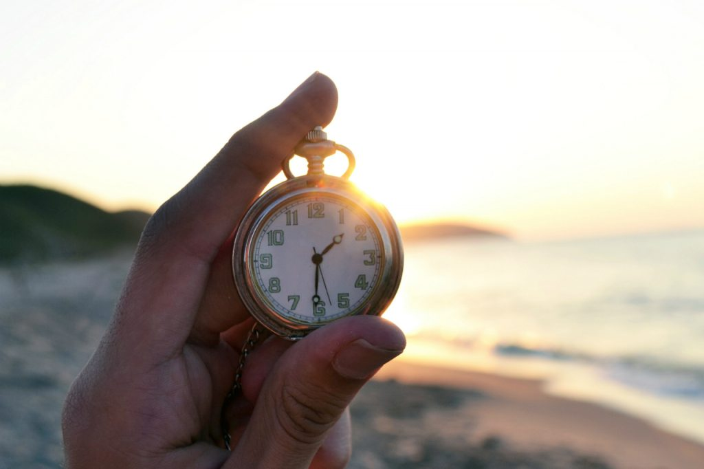 pocket watch being held with sunset background