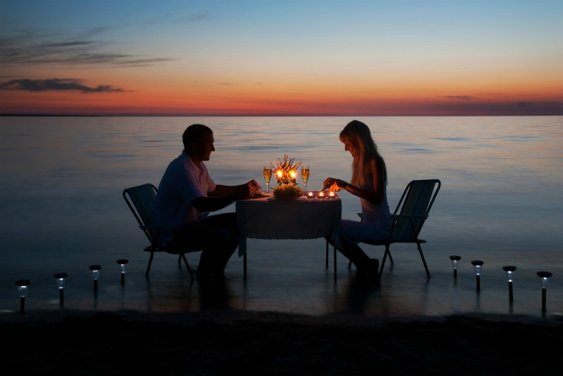 image of a couple having a romantic meal by the sea