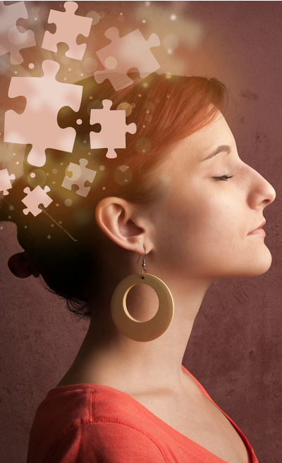 Image of a woman with closed eyes and puzzle pieces floating out of her head