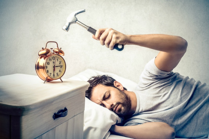 Image of a man hitting an alarm clock with a hammer