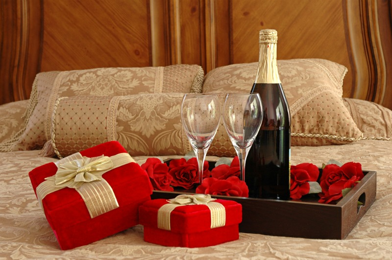 Image of rose petals, champagne and gifts