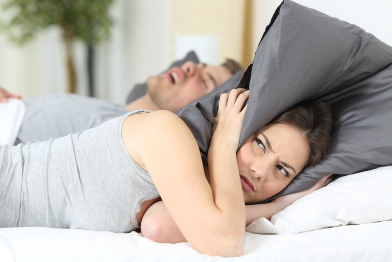 Image of a woman with pillow over ears