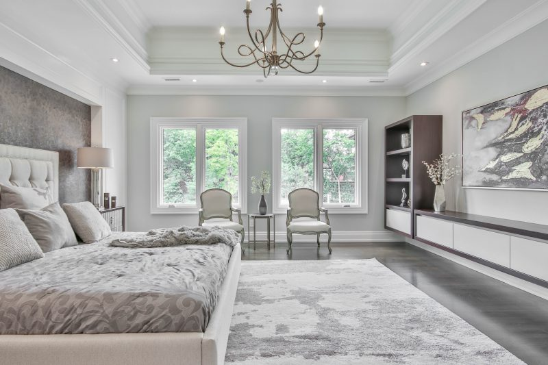 image of bedroom with chandelier and wall panelling to show neo-classical bedroom design trend