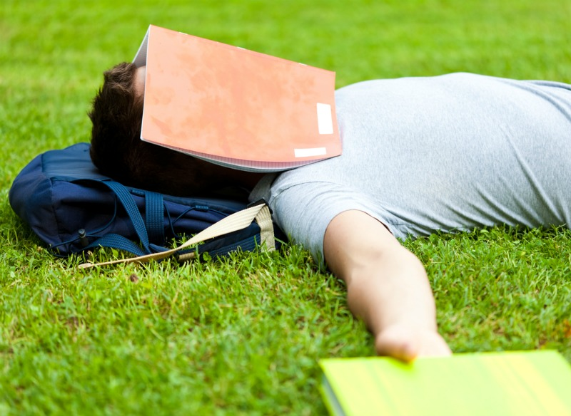 Student sleeping on grass with books over his face