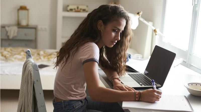 Teenager working at her desk in bedroom