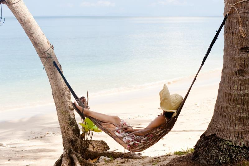 Woman asleep on beach in hammock
