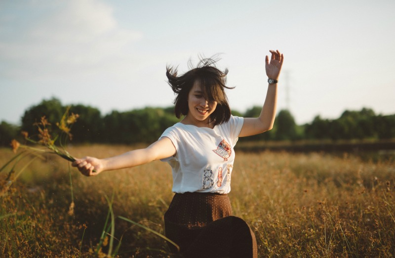 A woman dancing happily through a field holding some flowers in her hand