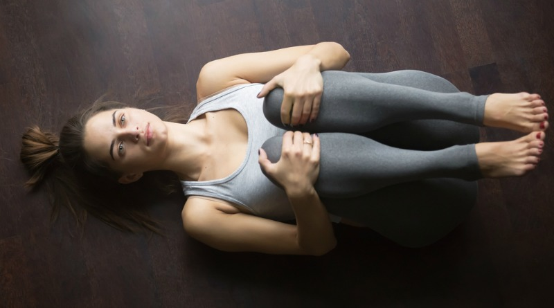 woman doing knee to chest stretch to relieve aches and pains