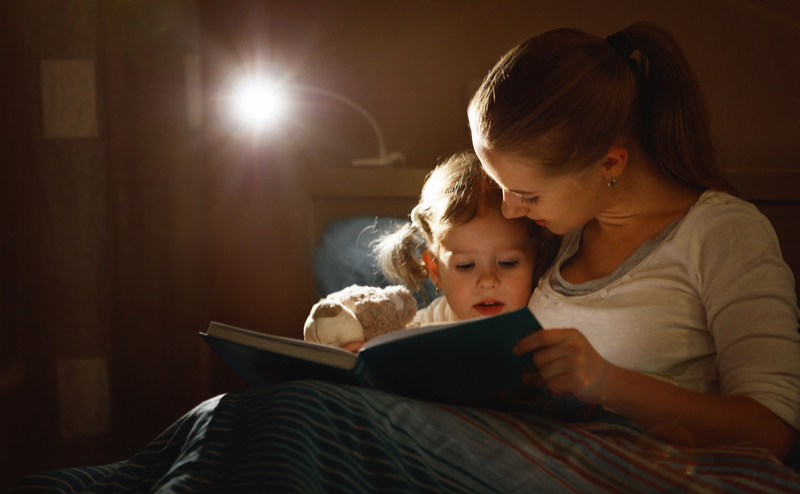 Woman reading bedtime story to child
