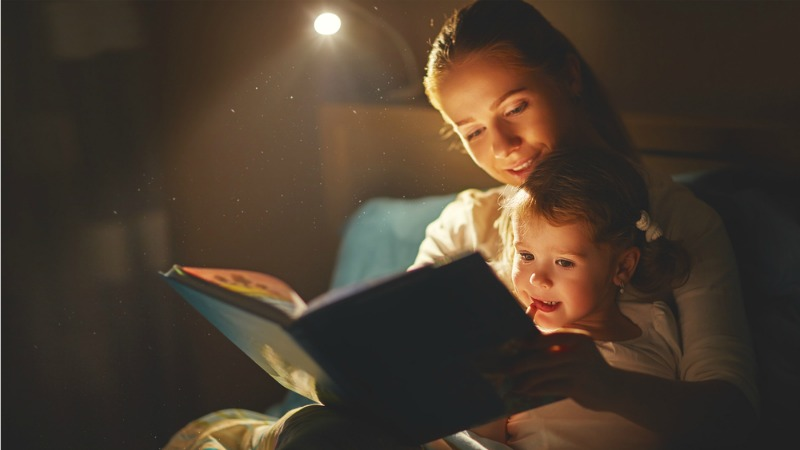 woman reading child a bedtime story